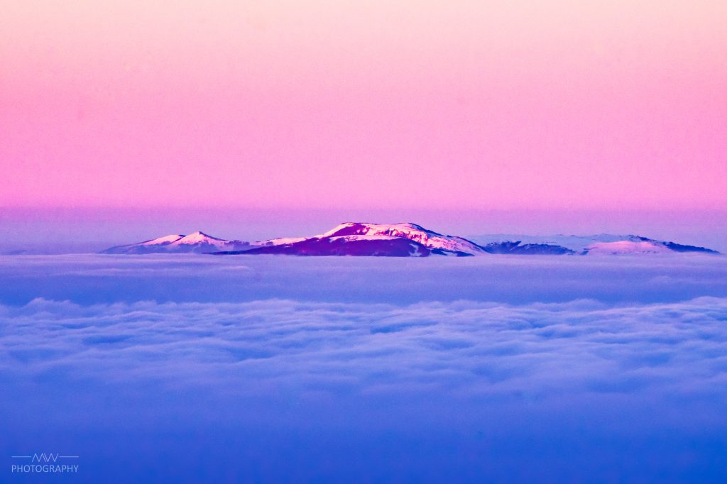 Mountain over clouds during sunset
