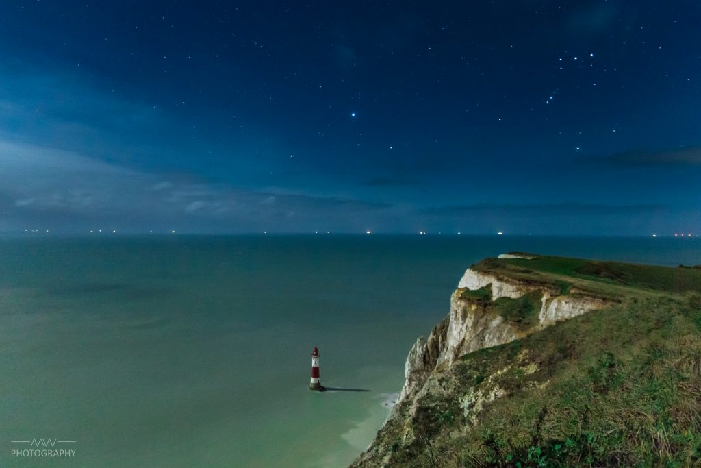 The belt of Orion shone high above the chalk cliff tops of beachy head at night.